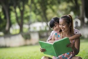 madre e figlia che leggono una favola a sua figlia nel parco foto