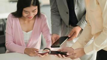 i giovani impiegati utilizzano gli smartphone per scambiare dati sui social media. foto