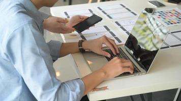 il team ux sta progettando un'applicazione per smartphone con laptop in un ufficio moderno. foto