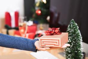 Imprenditrice mano azienda confezione regalo in vacanza di Natale in ufficio con decorazioni di Natale sul tavolo. foto
