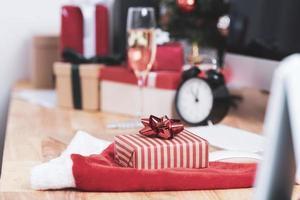 confezione regalo rossa durante le vacanze di natale in ufficio con decorazioni natalizie sul tavolo. foto