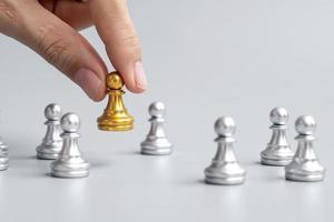 mano che tiene pezzi di pedina degli scacchi d'oro o uomo d'affari leader con uomini d'argento. vittoria, leadership, successo aziendale, squadra, reclutamento e concetto di lavoro di squadra foto
