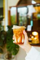 mano che tiene il bicchiere di caffè macchiato al caramello foto