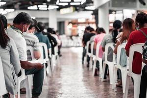 bangkok thailandia 25 agosto 2021. persone sedute su una sedia bianca, in attesa di essere vaccinate per prevenire la diffusione della polmonite da coronavirus covid-19. foto