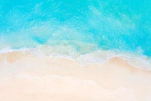 estate mare belle onde, acqua di mare blu in una giornata di sole. vista dall'alto dal drone. vista aerea del mare, incredibile sfondo di natura tropicale. bellissimo mare luminoso con spruzzi di onde e concetto di spiaggia di sabbia foto