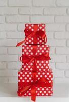 mucchio di scatole regalo rosse su sfondo muro bianco foto