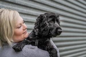 giovane donna che tiene il suo cane cocker spaniel su sfondo grigio muro esterno foto