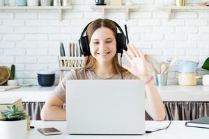 sorridente ragazza adolescente seduta alla scrivania in cucina che impara usando il suo laptop, salutando con la mano chiacchierando con gli amici foto