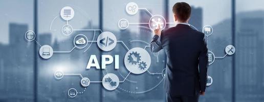 Interfaccia di programmazione applicazioni. strumento di sviluppo software API. concetto di tecnologia dell'informazione. l'uomo d'affari preme l'icona del testo API su un'interfaccia virtuale foto