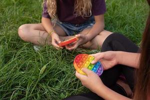 le ragazze giocano il popolare giocattolo pop-it in silicone colorato all'aperto sull'erba verde foto