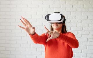 sorridi donna felice che fa esperienza con gli occhiali vr-auricolare della realtà virtuale a casa molto gesticolando le mani foto