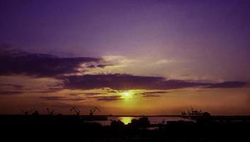 porto di Norfolk e gru al tramonto foto