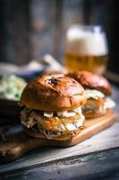 hamburger di pesce rustico con insalata di cavolo e birra foto