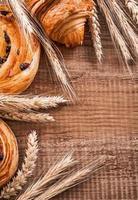 spighe di grano dorato uva passa rotoli cornetto su tavola di legno di quercia foto