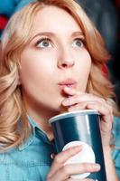 giovane donna con entusiasmo bere coca cola al cinema foto