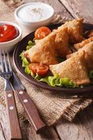 Samosa vegetariani su un piatto con pomodori e lattuga verticale foto