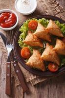 Samosa indiano sul piatto con il primo piano della salsa, vista superiore verticale