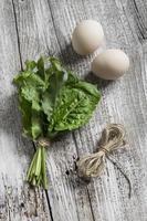 spinaci freschi e uova su uno sfondo in legno chiaro