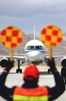 aeroporto - un personale dell'aeroporto dirige un aeromobile in posizione nell'aeroporto foto