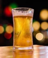 bicchiere di birra con scena di bar bokeh in background.