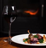 anatra arrosto con pastinaca e un bicchiere di vino rosso foto