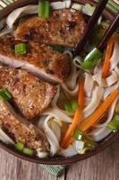zuppa con anatra e tagliatelle di riso macro. vista dall'alto verticale foto