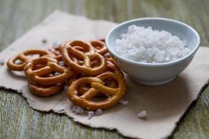 Ciambelline salate con sale su fondo di legno foto