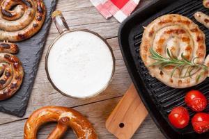 boccale di birra, gamberi alla griglia, salsicce e pretzel foto