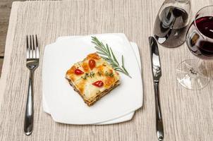 porzione di lasagne sul tavolo di legno foto
