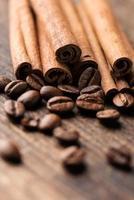 bastoncini di caffè e cannella su sfondo di legno vicino vertica