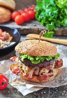 hamburger di manzo fatto in casa con cipolle fritte su uno sfondo di legno