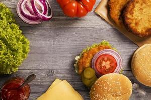 hamburger di pollo con formaggio, lattuga, pomodoro e cipolla