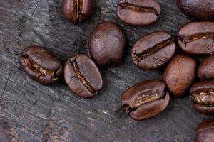 chicco di caffè su fondo in legno (legna che brucia) foto