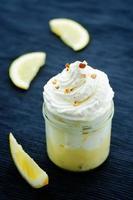 dessert a strati con crema al limone, gelato e panna montata foto