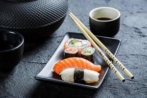 primo piano di sushi fresco servito in una ceramica nera foto