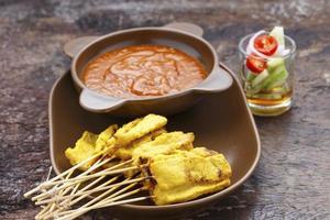 satay di maiale alla griglia con salsa di arachidi e aceto sul tavolo foto
