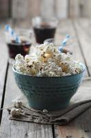 popcorn e cola sul tavolo di legno foto