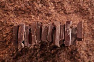 pezzi di cioccolato su sfondo di cacao grattugiato foto