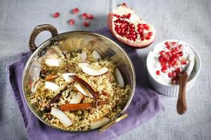 piatto di riso indiano biryani con raita di cocco e melograno foto