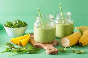 frullato verde sano con banana di mango di spinaci in barattoli di vetro foto