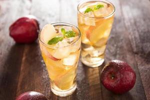 succo di mela e mele sul tavolo di legno foto