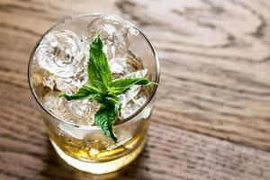 bicchiere di rum sullo sfondo di legno foto