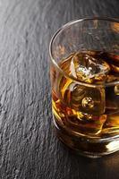 bicchiere di whisky con ghiaccio sul tavolo di pietra nera foto