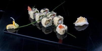Sushi Uramaki su un piatto nero foto