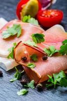 fette arricciate di delizioso prosciutto con foglie di prezzemolo foto