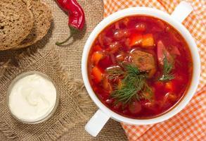 borsch in una ciotola bianca. zuppa tradizionale di barbabietola rossa. foto