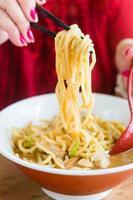 donna che mangia stile giapponese dell'alimento della tagliatella foto