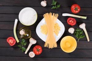 pasta cruda, pomodori, funghi, farina e uova foto