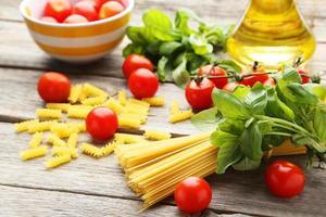 spaghetti, basilico e pomodori su fondo di legno grigio