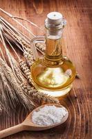cucchiaio di legno con farina orecchie di olio di bottiglia di grano su foto
